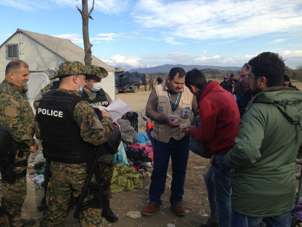 Border police examine asylum seekers' documents at the Greek-Macedonian border.